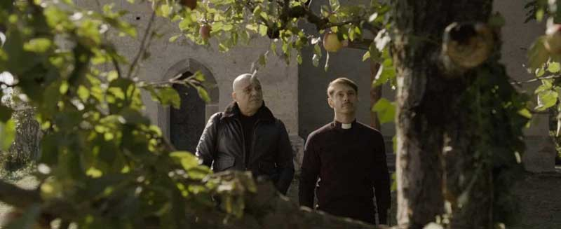 Adamo (Claudio Amendola) e padre Ivan (Giorgio Pasotti) sotto all'albero di mele